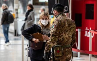 MILAN, ITALY - MARCH 10: An Italian soldier speaks to a passenger at Milano Centrale train station on March 10, 2020 in Milan, Italy. The Italian Government has taken the unprecedented measure of a nationwide lockdown, limiting people to move only for work or health reasons, in an effort to fight the world's second-most deadly coronavirus outbreak outside of China. (Photo by Emanuele Cremaschi/Getty Images