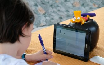 MILAN, ITALY - MAY 06: Fourth grade student Nicolo, 10, son of the photographer, uses a tablet to participate in an E-learning class with his teacher and classmates while at home on May 06, 2020 in Milan, Italy. Italy will remain on lockdown to stem the transmission of the Coronavirus (Covid-19), slowly easing restrictions.  (Photo by Pier Marco Tacca/Getty Images)