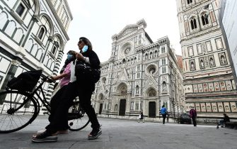 FLORENCE, ITALY - MAY 13:  People walk through the Piazza del Duomo Santa Maria del Fiore empty of tourists  on May 13, 2020 in Florence, Italy. (Photo by Roberto Serra - Iguana Press/Getty Images)
