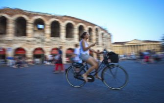 VERONA, ITALY - JULY 14:  (EDITORS NOTE: Exposure latitude of this composite image has been digitally increased) Woman on a bicycle is riding  in front of the Arena of Verona on July 14, 2010 in Verona, Italy. The famous Arena di Verona is popular for the annual opera festival in summer. The arena is one of the largest ancient roman amphitheatres. It was built in 30 A.C. and belongs to the Unesco World Heritage.  (Photo by EyesWideOpen/Getty Images)