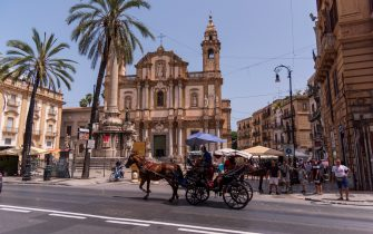 """PALERMO, ITALY - AUGUST 8: Horse-Drawn Carriage in motion  front of Church of Saint Dominic that is the second most important church of Palermo after the ancient cathedral. It is located in Piazza San Domenico, in the quarter of the Loggia, within the historic centre of Palermo. The church hosts the burials of many eminent figures of Sicilian history and culture. For this reason it is known as the """"Pantheon of illustrious Sicilians"""".on August 8, 2019 in Palermo, Italy. (Photo by Stefano Montesi - Corbis/Getty Images)"""