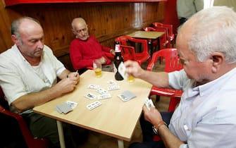 Anziani giocano a carte in un bar a Napoli in una foto d'archivio. ANSA / CIRO FUSCO