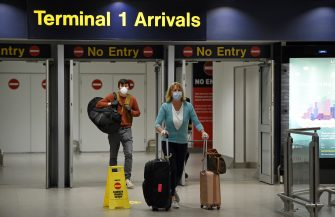 Passenger swearing PPE (personal protective equipment), including a face mask as a precautionary measure against COVID-19, push their suitcases after arriving at Terminal 1 of Manchester Airport in northern England, on June 8, 2020, as the UK government's planned 14-day quarantine for international arrivals to limit the spread of the novel coronavirus begins. (Photo by Oli SCARFF / AFP) (Photo by OLI SCARFF/AFP via Getty Images)