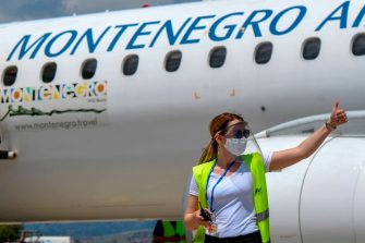 An airport personal gestures at Podgorica's airport on June 12, 2020, as the national airline, Montenegro Airlines, has started with commercial flights after an almost three-month suspension of flights due to the spread of the COVID-19 (the novel coronavirus). (Photo by Savo PRELEVIC / AFP) (Photo by SAVO PRELEVIC/AFP via Getty Images)