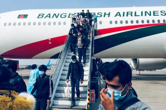 Bangladeshi nationals disembark from a Biman Bangladesh Airlines' plane at the tarmac of Hazrat Shahjalal International Airport following their evacuation from the Chinese city of Wuhan, in Dhaka on February 1, 2020. - A virus similar to the SARS pathogen has killed 259 people in China and spread around the world since emerging in a market in the central Chinese city of Wuhan. (Photo by STR / AFP) (Photo by STR/AFP via Getty Images)