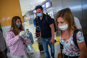 Passengers of a flight from Paris wearing protective face masks arrive at the Eleftherios Venizelos International Airport in Athens on June 15, 2020, as Greece's two main airports in Athens and Thessaloniki reopen to arrivals from 29 countries, at the start of the tourist season. (Photo by ANGELOS TZORTZINIS / AFP) (Photo by ANGELOS TZORTZINIS/AFP via Getty Images)