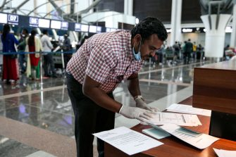 A man wearing latex gloves and a mask, due to the COVID-19 coronavirus pandemic, checks airline tickets and travel documents while behind him Indian nationals residing in Oman queue with their luggage at the check-in counter at a terminal in Muscat International Airport ahead of their repatriation flight from the Omani capital, on May 12, 2020. (Photo by MOHAMMED MAHJOUB / AFP) (Photo by MOHAMMED MAHJOUB/AFP via Getty Images)