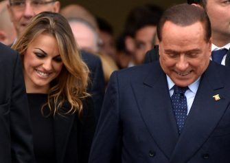 """Italian former Prime Minister Silvio Berlusconi (R), flanked by his girlfriend Francesca Pascale, leaves after the People of Freedom (PDL) party's national convention in Rome on November 16, 2013. Silvio Berlusconi hit out at members of his centre-right party who want to """"murder"""" him politically as an internal split provoked the scandal-tainted ex-premier's ire on November 16.  Following late-night talks, Berlusconi's former right-hand man Angelino Alfano announced he would not remain at the side of his onetime mentor and would form a separate parliamentary grouping instead.   AFP PHOTO / ALBERTO PIZZOLI        (Photo credit should read ALBERTO PIZZOLI/AFP via Getty Images)"""