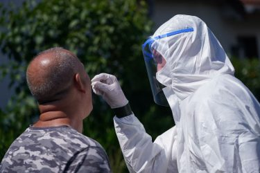 GUETERSLOH, GERMANY - JUNE 23: A soldier of the Bundeswehr dressed in full PPE takes a throat swab sample from a local resident in the town of Rheda following a Covid-19 outbreak at the nearby Toennies meat packaging plant during the coronavirus pandemic on June 23, 2020 near Guetersloh, Germany. State authorities announced today they are placing the entire Guetersloh region into lockdown following confirmed Covid-19 infection in over 1,500 employees of the plant. The Bundeswehr, the German armed forces, has stepped in to help test people at the approximately 250 houses and apartment complexes where Toennies employees, many of whom come from Romania, Bulgaria and Poland, live throughout the Guetersloh region. (Photo by Sean Gallup/Getty Images)