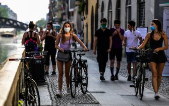 People stroll along the Navigli canals in Milan on May 8, 2020 during the country's lockdown aimed at curbing the spread of the COVID-19 infection, caused by the novel coronavirus. (Photo by Miguel MEDINA / AFP) (Photo by MIGUEL MEDINA/AFP via Getty Images)