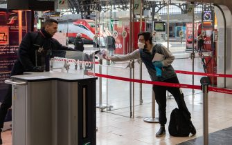 """MILAN, ITALY - MARCH 08: A man, wearing gloves and a face mask, shows his ticket to a steward as he goes through security control at Milan's Central Station on March 08, 2020 in Milan, Italy. Prime Minister Giuseppe Conte announced overnight a """"national emergency"""" due to the coronavirus outbreak and imposed quarantines on the Lombardy and Veneto regions, which contain roughly a quarter of the country's population. Italy has the highest number of cases and fatalities in Europe. (Photo by Emanuele Cremaschi/Getty Images)"""