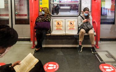 Commuters sit in a coach at the Cardona underground metro station, with red circles on the ground indicating where to stand to maintain distance, on May 4, 2020 in Milan, as Italy starts to ease its lockdown, during the country's lockdown aimed at curbing the spread of the COVID-19 infection, caused by the novel coronavirus. - Stir-crazy Italians will be free to stroll and visit relatives for the first time in nine weeks on May 4, 2020 as Europe's hardest-hit country eases back the world's longest nationwide coronavirus lockdown. (Photo by Miguel MEDINA / AFP) (Photo by MIGUEL MEDINA/AFP via Getty Images)