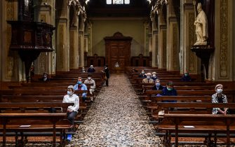 TOPSHOT - Residents wearing a face mask attend a morning mass at San Biagio and Santa Maria Immacolata church on May 20, 2020 in Codogno, southeast of Milan, one of the villages at the epicenter of the coronavirus epidemic in February, as the country's is easing its lockdown aimed at curbing the spread of the COVID-19 infection, caused by the novel coronavirus. (Photo by Miguel MEDINA / AFP) (Photo by MIGUEL MEDINA/AFP via Getty Images)