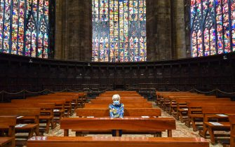 TOPSHOT - A woman attends a mass at the Cappella Feriale of the Duomo cathedral in Milan on May 18, 2020 during the country's lockdown aimed at curbing the spread of the COVID-19 infection, caused by the novel coronavirus. - Restaurants and churches reopen in Italy on May 18, 2020 as part of a fresh wave of lockdown easing in Europe and the country's latest step in a cautious, gradual return to normality, allowing businesses and churches to reopen after a two-month lockdown. (Photo by Miguel MEDINA / AFP) (Photo by MIGUEL MEDINA/AFP via Getty Images)