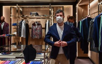 A customer tries on a jacket at an Etro fashion shop on May 18, 2020 in Milan during the country's lockdown aimed at curbing the spread of the COVID-19 infection, caused by the novel coronavirus. - Restaurants and churches reopen in Italy on May 18, 2020 as part of a fresh wave of lockdown easing in Europe and the country's latest step in a cautious, gradual return to normality, allowing businesses and churches to reopen after a two-month lockdown. (Photo by Miguel MEDINA / AFP) (Photo by MIGUEL MEDINA/AFP via Getty Images)