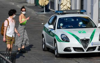 Municipal policemen wearing a face mask patrol in a car along the Navigli canals in Milan on May 8, 2020 during the country's lockdown aimed at curbing the spread of the COVID-19 infection, caused by the novel coronavirus. (Photo by Miguel MEDINA / AFP) (Photo by MIGUEL MEDINA/AFP via Getty Images)