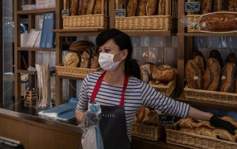 MILAN, ITALY - MARCH 11: A shop assistant serves some bread in a french bakery on March 11, 2020 in Milan, Italy. The Italian Government has strengthened up its quarantine rules, shutting all commercial activities except for pharmacies, food shops, gas stations, tobacco stores and news kiosks in a bid to stop the spread of the novel coronavirus. (Photo by Emanuele Cremaschi/Getty Images)
