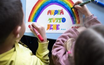 MILAN, ITALY - MARCH 13:  Children draw a rainbow and the slogan of hope being shared in Italy â  Andrà tutto bene.â   (Everything will be alright.) during quarantine measures amid the novel coronavirus COVID-19 pandemic on March 13, 2020 in Milan, Italy. Italy, which has seen the worst COVID-19 outbreak outside of China, tightened quarantine restrictions on Thursday, closing all commercial activities except supermarkets, pharmacies and banks.  (Photo by Pietro D'Aprano/Getty Images)