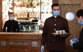 A waiter at Caffe Cracco handles takeaway coffee on May 4, 2020 in Milan as Italy starts to ease its lockdown, during the country's lockdown aimed at curbing the spread of the COVID-19 infection, caused by the novel coronavirus. - Stir-crazy Italians will be free to stroll and visit relatives for the first time in nine weeks on May 4, 2020 as Europe's hardest-hit country eases back the world's longest nationwide coronavirus lockdown. (Photo by Miguel MEDINA / AFP) (Photo by MIGUEL MEDINA/AFP via Getty Images)