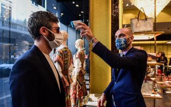 A customer (L) undergoesa body temperature scanning procedure at an Etro fashion shop on May 18, 2020 in Milan during the country's lockdown aimed at curbing the spread of the COVID-19 infection, caused by the novel coronavirus. - Restaurants and churches reopen in Italy on May 18, 2020 as part of a fresh wave of lockdown easing in Europe and the country's latest step in a cautious, gradual return to normality, allowing businesses and churches to reopen after a two-month lockdown. (Photo by Miguel MEDINA / AFP) (Photo by MIGUEL MEDINA/AFP via Getty Images)