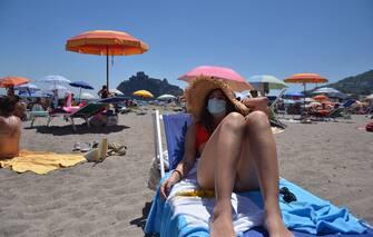 Una donna indossa una mascherina chirurgica in spiaggia