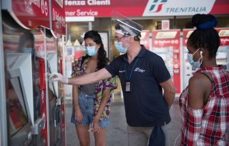 TURIN, ITALY - JUNE 03: A train attendant wear a protective mask and gloves helps two travellers to buy train tickets from an automatic ticket machine at the Porta Nuova railway station on June 03, 2020 in Turin, Italy. Today 3 June the Italian government has reopened the regional borders thus giving Italians the opportunity to move between the regions again and be able to go to relatives and go on holiday within the Italian borders. Many Italian businesses have been allowed to reopen, after more than two months of a nationwide lockdown meant to curb the spread of Covid-19. (Photo by Stefano Guidi/Getty Images)