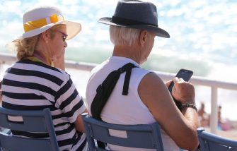 An elderly man uses a mobile phone while sitting on the Promenades des Anglais beachfront in the French riviera city of Nice on September 1, 2017.  In a largely saturated telecommunications market, there is still a large share of the population that remains under-equipped and offers growth prospects: senior citizens. / AFP PHOTO / VALERY HACHE        (Photo credit should read VALERY HACHE/AFP via Getty Images)