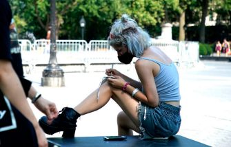 NEW YORK, NEW YORK - JULY 21: A person walks past a woman writing on her knee as the city enters Phase 4 of re-opening following restrictions imposed to slow the spread of coronavirus on July 21, 2020 in New York City. The fourth phase allows outdoor arts and entertainment, sporting events without fans and media production. (Photo by John Lamparski/Getty Images)