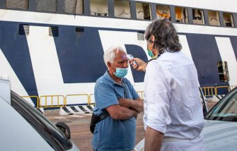 OLBIA, ITALY - JULY 08: A passenger wearing a face mask has his temperature taken by a ferry crew member on July 08, 2020 in Olbia, Italy. The Olbia Livorno ferry route connects Sardinia with Italy and is operated by two ferry companies, the Moby Lines and the Grimaldi Lines. Safety and social distancing measures are still in place due to the Covid-19 pandemic. (Photo by Max Cavallari/Getty Images)