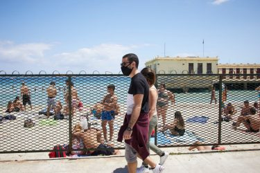 PALERMO, ITALY - JUNE 07:  A man and woman wearing protective mask walks on Mondello beach on the first day of the reopening of the bathing facilities on June 07, 2020 in Palermo, Italy. Many Italian businesses have been allowed to reopen, after more than two months of a nationwide lockdown meant to curb the spread of Covid-19. (Photo by Lorenzo Palizzolo/Getty Images)