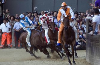 Jockey Jonathan Bartoletti (R), named Scompiglio, of Leocorno parish leads to win the Palio horse race at the Casato curve in the Piazza del Campo in Siena, 16 Agoust 2007. The popular Italian horse race, the Palio of Siena celebrates the apparition of the Assunta virgin. AFP PHOTO / NICO CASAMASSIMA. (Photo credit should read NICO CASAMASSIMA/AFP via Getty Images)
