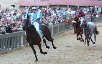 SIENA, ITALY - AUGUST 16: (RESTRICTED TO EDITORIAL USE - NO MARKETING, NO ADVERTISING CAMPAIGNS)  Giovanni Atzeni (L), known as Tittia, rides his horse bareback on his way to winning the Palio dell'Assunta horse-race at Piazza del Campo square on August 16, 2013 in Siena, Italy. The Palio races in Siena, in which riders representing city districts compete, and takes place twice a year in the summer in a tradition that dates back to 1656. (Photo by Chris Jablinski/Getty Images)
