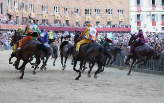 SIENA, ITALY - AUGUST 16: (RESTRICTED TO EDITORIAL USE - NO MARKETING, NO ADVERTISING CAMPAIGNS) Competitors race riding bareback during the annual Palio dell'Assunta horse-race at the Piazza del Campo Square on August 16, 2013 in Siena, Italy. The Palio races in Siena, in which riders representing city districts compete, and takes place twice a year in the summer in a tradition that dates back to 1656. (Photo by Chris Jablinski/Getty Images)