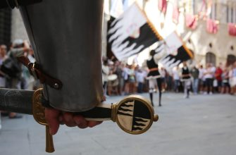 SIENA, ITALY - AUGUST 16: Members of the Contrada della Lupa walk the streets during a procession before the annual Palio dell'Assunta horse-race on August 16, 2013 in Siena, Italy.The so-called Duce holds a word, while flag-swingers act in the background. The Palio races in Siena, in which riders representing city districts compete,and takes place twice a year in the summer in a tradition that dates back to 1656.