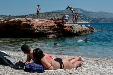 Sunbathers watch a young man doing a backflip into the water as they lie on the beach in Athen's southern suburb on May 9, 2020, as the nations readies for the reopening of schools and most of shops starting May 11. (Photo by Louisa GOULIAMAKI / AFP) (Photo by LOUISA GOULIAMAKI/AFP via Getty Images)