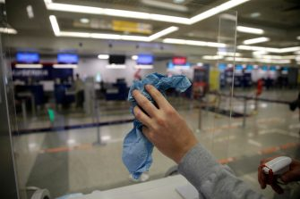 epa08435329 Airport personnel wipes a plexiglas window at the check-in counters at the Belgrade Nikola Tesla Airport in Belgrade, Serbia, 21 May 2020. Air travel has resumed with a limited number of flights after the authorities in Serbia approved the airport to gradually resume operations with new guidelines amid the COVID-19 pandemic. Only passengers with tickets are allowed into the airport building four hours ahead of their flight.  EPA/ANTONIO BAT