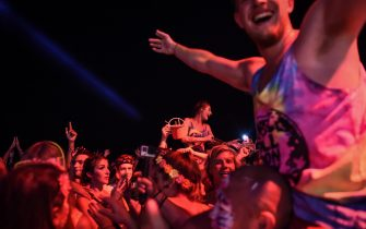 Partygoers dance on the beach during the Full Moon Party on Ko Phangan island in the southern Thai province of Surat Thani on the night of December 14, 2016. Foreign tourists are returning in droves to the popular party island of Ko Phangan for the infamous Full Moon Party after restrictions on celebrations were eased months after the death of Thai King Bhumibol Adulyadej on October 13. / AFP / LILLIAN SUWANRUMPHA        (Photo credit should read LILLIAN SUWANRUMPHA/AFP via Getty Images)