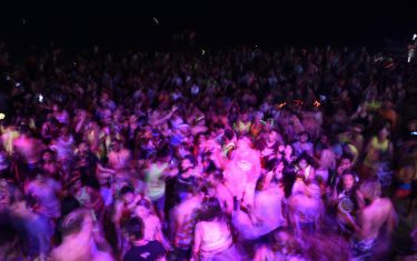 Thousands of partygoers dance on the beach during the Full Moon Party on Ko Phangan island in the southern Thai province of Surat Thani on the night of December 14, 2016. Foreign tourists are returning in droves to the popular party island of Ko Phangan for the infamous Full Moon Party after restrictions on celebrations were eased months after the death of Thai King Bhumibol Adulyadej on October 13. / AFP / LILLIAN SUWANRUMPHA        (Photo credit should read LILLIAN SUWANRUMPHA/AFP via Getty Images)