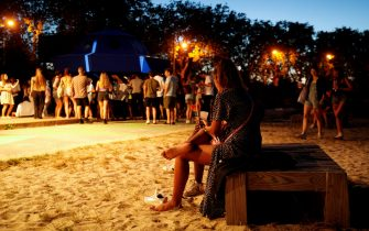 """A woman sits on a bench next to people enjoying an open air party in Saint-Denis, north of Paris on August 1st, 2020. - It took an epidemic, the closure of clubs and a relative permissiveness of the authorities for Paris to become in one summer a sanctuary of the """"free party"""", these underground techno parties, some of which gathered in July, up to a thousand of people. The epicenter of this phenomenon is in the Bois de Vincennes, where a dozens of musical scenes are set illegally in the depths of the woods. (Photo by GEOFFROY VAN DER HASSELT / AFP) (Photo by GEOFFROY VAN DER HASSELT/AFP via Getty Images)"""