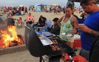 HUNTINGTON BEACH, CA - JULY 6:  Beach goers barbecue and gather around traditional beach bonfires on July 6, 2013 in Huntington Beach, California. Beach fires are a long- and strongly-held tradition of southern California beach and surfing communities. In a move that has angered many, the Newport Beach City Council asked the California Coastal Commission to allow the city to remove its beach fire rings, citing air quality concerns, in an action that could lead to the end of beach fires in much of southern California. The state Coastal Commission is poised to deny the city effort to remove the fire rings, however, the regional air quality board might approve a measure on July 12 that would allow the city to end beach bonfires.  (Photo by David McNew/Getty Images)