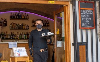 AGGIUS, ITALY - JUNE 06: A bar waiter wears gloves and a protective mask to serve coffee to his customers as required by the safety protocols for Covid-19. In the background, in addition to the sanitizing gel, a nice welcome message for its customers on June 06, 2020 in Aggius, Sardegna, Italy. Many Italian businesses have been allowed to reopen, after more than two months of a nationwide lockdown meant to curb the spread of Covid-19. (Photo by Emanuele Perrone/Getty Images)