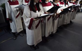 TO GO WITH AFP STORY CHINA-RELIGION-POLITICS-CHRISTMAS BY TOM HANCOCK     This photo taken on December 24, 2014 shows the choir of an underground church singing at a Christmas Eve service at an apartment in Beijing. China is now home to an estimated 70 million Christians, according to a 2011 survey by the Pew Research Center, as people search for a sense of community and meaning in a fast-changing society.  The vast majority of Chinese Protestants -- around 50 million, according to the survey -- shun state-run churches and worship in self-organising groups outside government-control. AFP PHOTO / Greg BAKER (Photo by Greg Baker / AFP) (Photo by GREG BAKER/AFP via Getty Images)