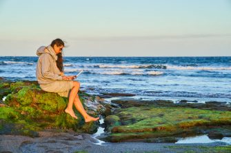 TENERIFE, SPAIN - JANUARY 19: Woman sits alone on the rocks with colorful seaweed working with a notebook at the beach on January 19, 2018 in El Medano, Tenerife, Spain. Model released (Photo by EyesWideOpen/Getty Images)