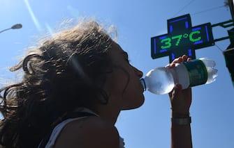 Una ragazza si disseta bevendo acqua fredda da una bottiglietta a Genova. 31  luglio 2018. Ondata di calore in Liguria con bollino rosso anche per il 2 agosto, prolungata dunque di altre 24 ore dal Ministero di Salute rispetto all'allerta diramato ieri. Arpal ha emesso un avviso meteorologico per avvertire dell'ondata di calore con elevato disagio a causa di temperature elevate e tassi d'umidità medio alti.    ANSA/LUCA ZENNARO