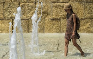 A woman cools herself in a fountain near the Ara Pacis monument, in central Rome on August 2, 2018. - Italy is experiencing its first summer heat wave with temperatures approaching 40 degrees Celsius. (Photo by Andreas SOLARO / AFP) (Photo by ANDREAS SOLARO/AFP via Getty Images)