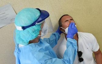 Coda delle persone rientrate dall'estero per fare il tampone all'ospedale Molinette, Torino, 23 agosto 2020 ANSA/ALESSANDRO DI MARCO