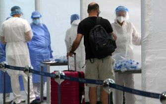 Health workers collect swabs and conduct tests on passengers for coronavirus disease (COVID-19) positivity at the Malpensa airport in Milan, Italy, 20 August 2020.  ANSA / MATTEO BAZZI