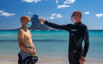 OLBIA, ITALY - JUNE 14: body temperature measurement before scuba diving and use of the projection mask. The manager of the diving center respects the rules imposed against the spread of Covid-19 on June 14, 2020 in Olbia, Italy. The whole country is returning to normality after more than two months of a nationwide lockdown meant to curb the spread of Covid-19. (Photo by Emanuele Perrone/Getty Images)