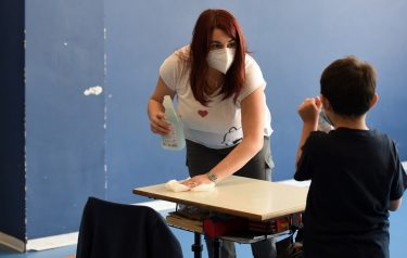 BORGOSESIA, ITALY - MAY 12:  A teacher  cleans a school desk with sanitary cleaner during a lesson in a classroom with school desks spaced apart to respect social distancing measures to counter the spread of COVID-19 on May 12, 2020 in Borgosesia, Italy. Italy was the first country to impose a nationwide lockdown to stem the transmission of the Coronavirus (Covid-19), but this project by the Borgosesia maYor aims to open schools with the correct safety measures.  (Photo by Pier Marco Tacca/Getty Images)