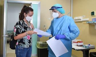 Un'addetta sanitaria dell ospedale Molinette effettua un tampone a una persona rientrata dalle ferie trascorese all estero, Torino, 23 agosto 2020 ANSA/ALESSANDRO DI MARCO